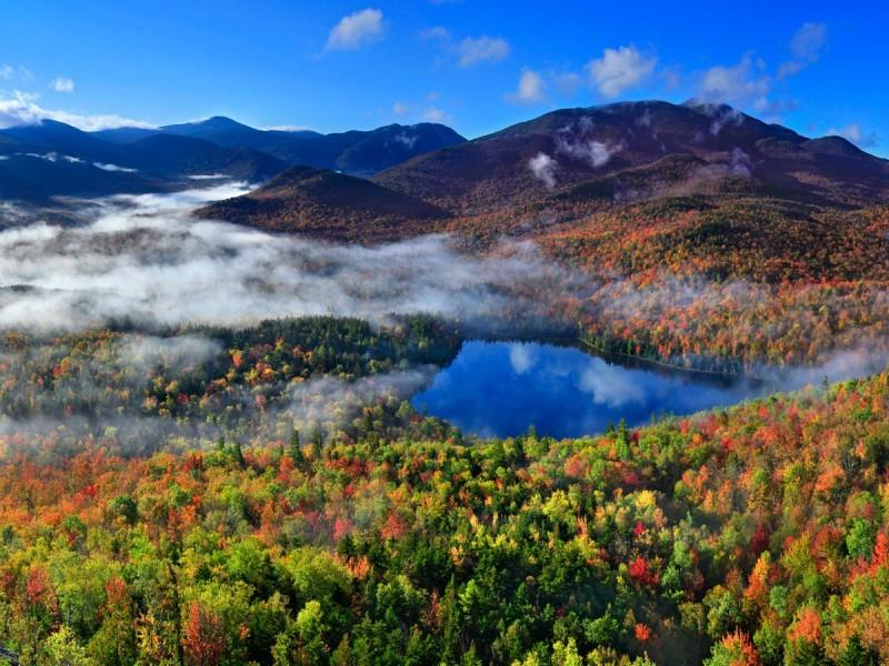 Picture from the top of a mountain of green pine trees amongst fall foliage and in the middle of the picture is a blue lake along the photo is fog laying in the valleys of the mountains