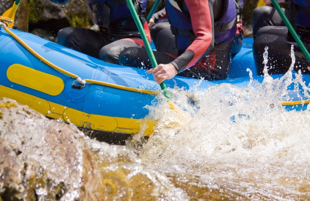 The shoulders down of individuals on a raft white water rafting and water splashing up the tube