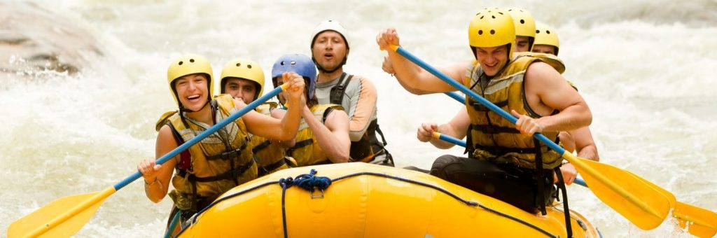 Individuals in lifejackets and helmets white water rafting in a tube with water splashing around them