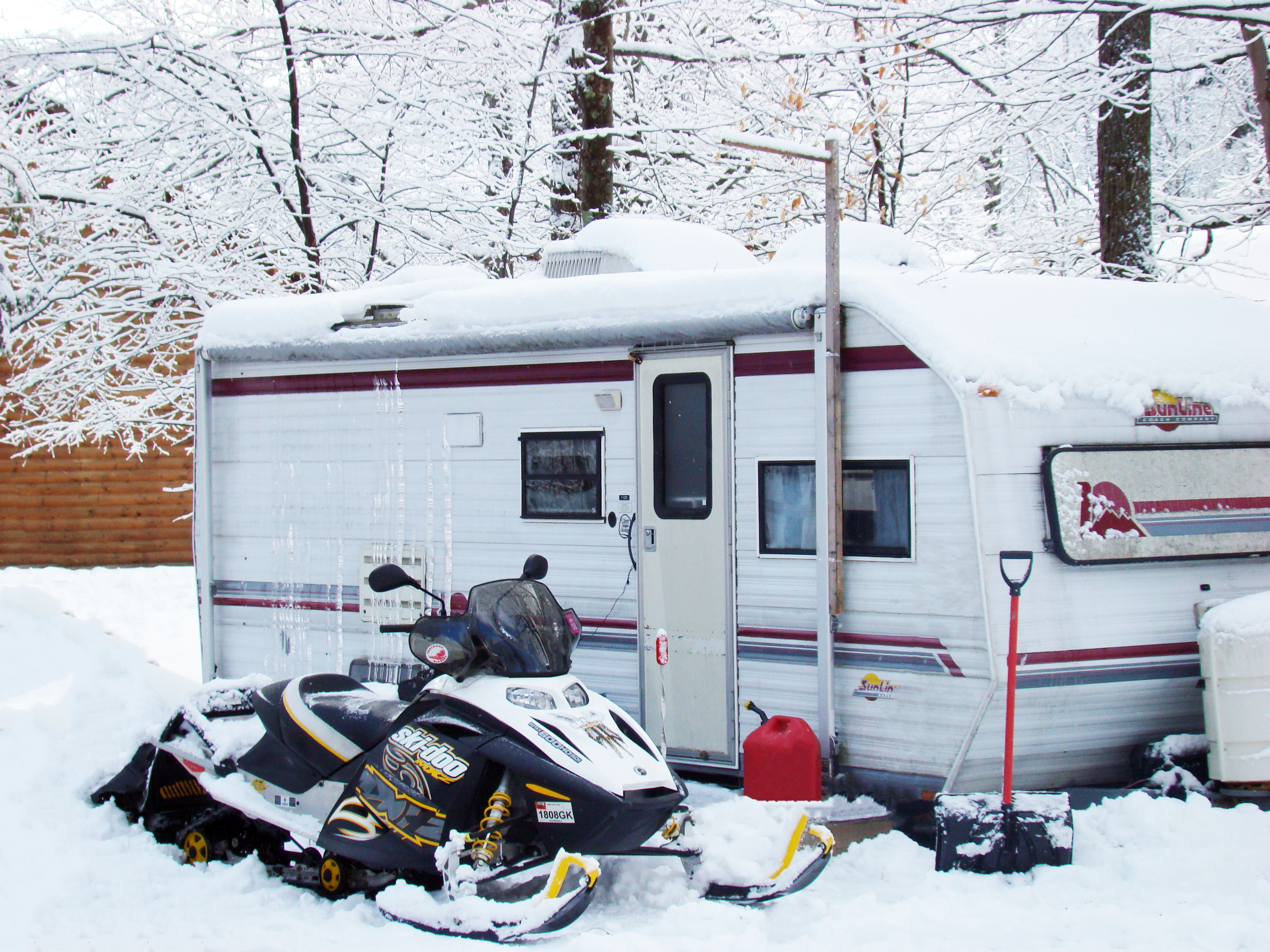 An RV and snowmobile surrounded by the snow and the snow covered trees.