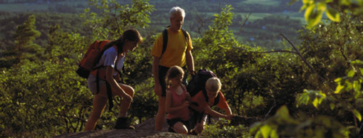 A family on a hiking trail surrounded by green foliage