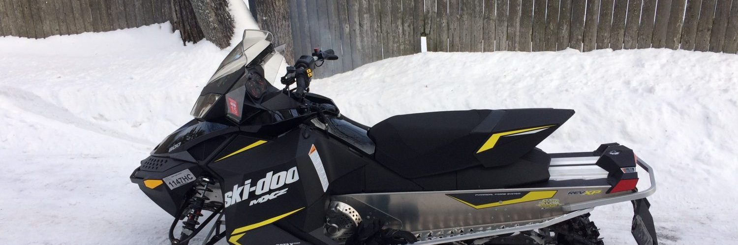 A black and yellow snowmobile is ready to hit the snowmobiling trails.