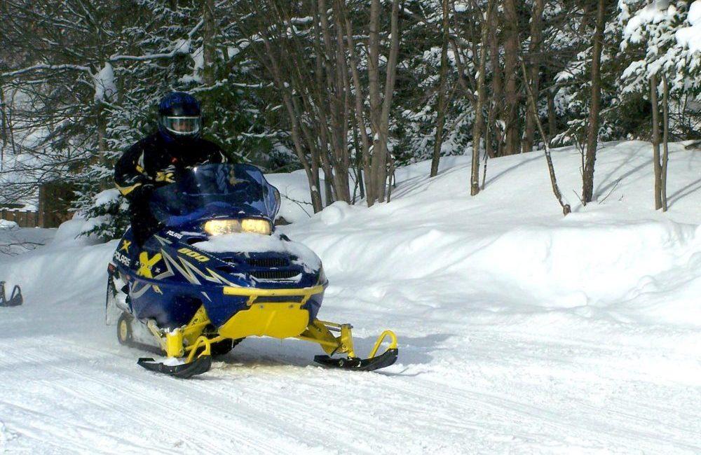 A snowmobiler snowmobiling on a trail