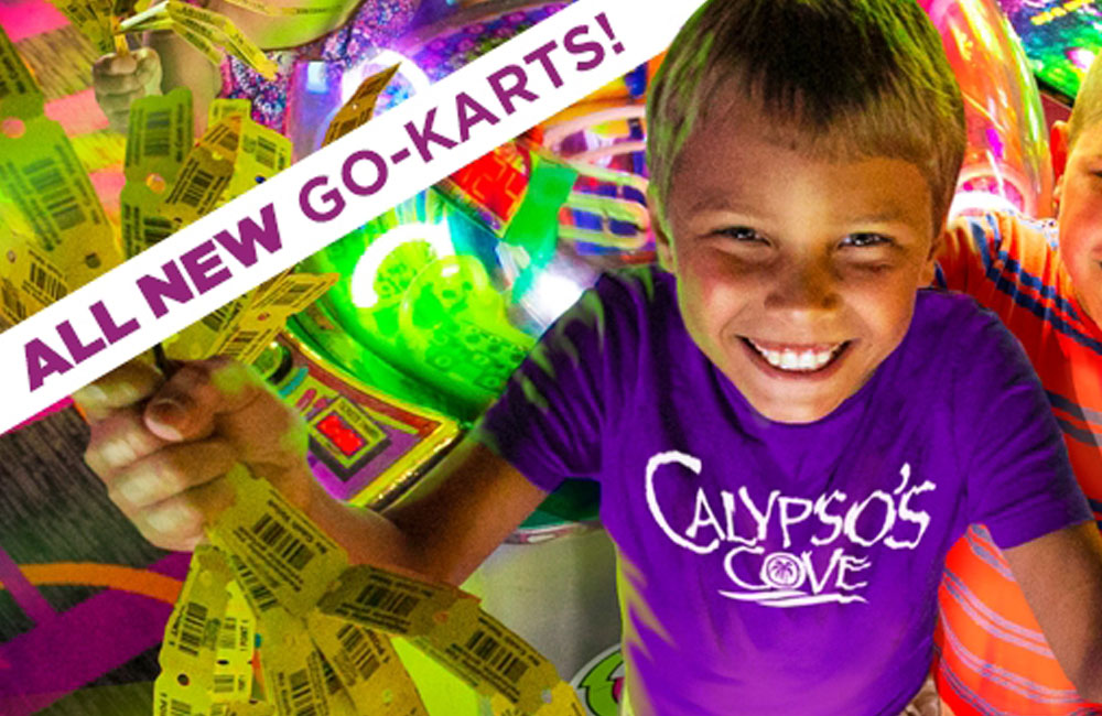 happy kid holding tickets with all new go-karts written next to him