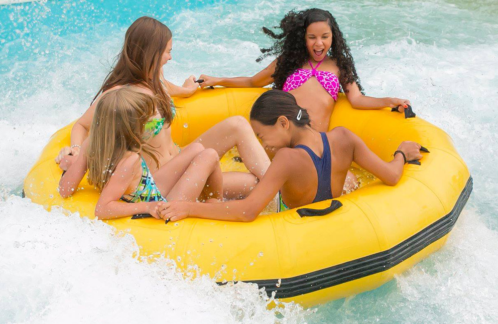 Four girl friends laughing and sitting on a tube as water splashes around them