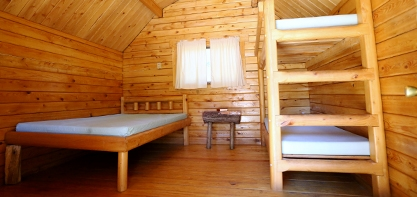 The inside of a cottage with all wood flooring, walls, and ceiling with a window with soft white curtains and a wooden bed next to a night stand and on thee other side is a wooden bunk bed