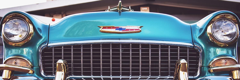 An antique Chevy car. The car is a shiny blue color.