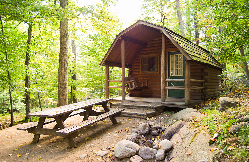 One of the cabin rentals available at the Camping Resort. This cabin has a picnic table and a wooden swing in the front.