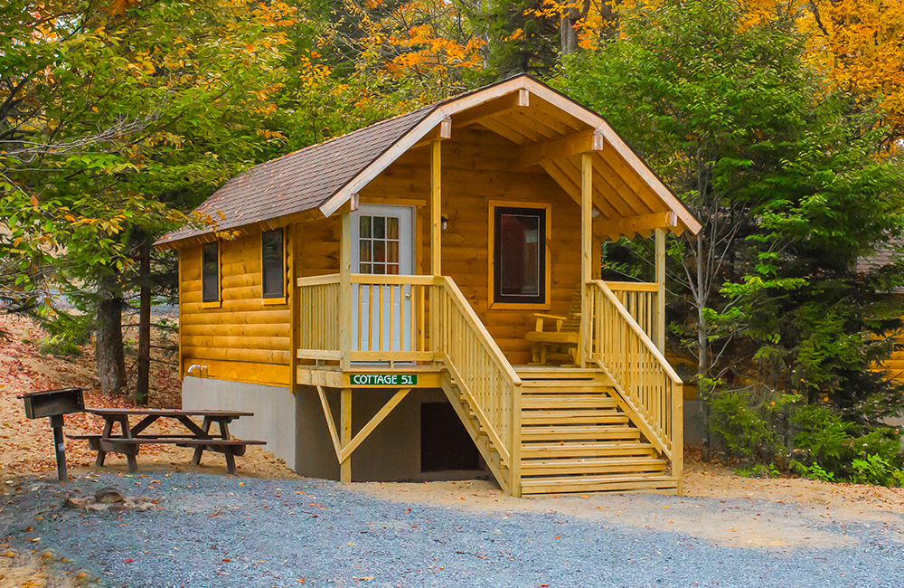 One of the cottages that guests can rent. This rental has a picnic table and a wooden bench in the front.