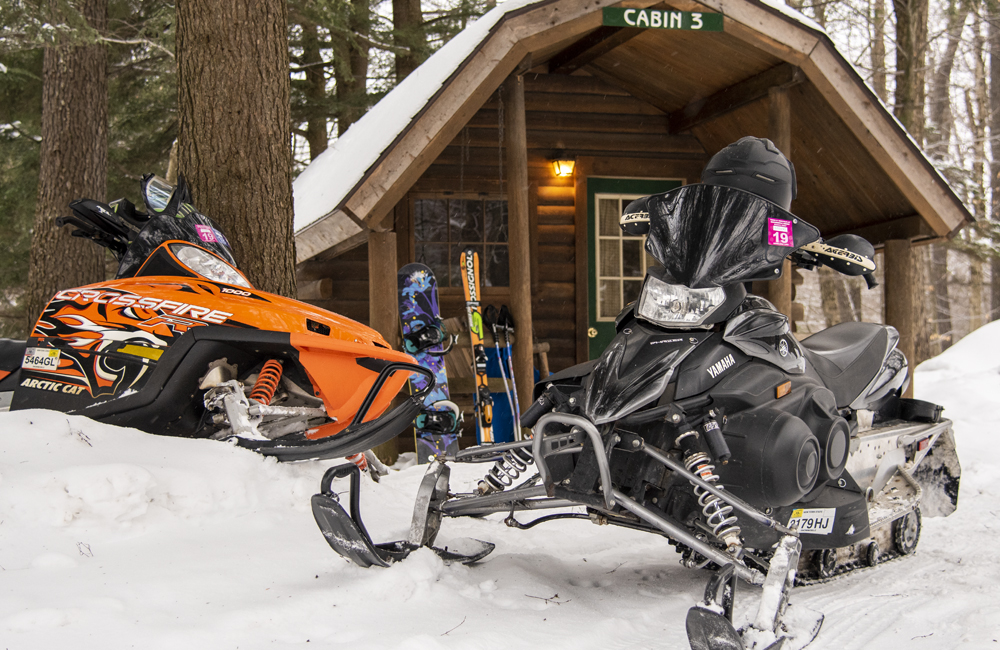 Two snowmobiles are in front of one of the cabins at Old Forge Camping Resort.