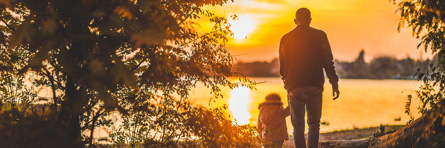 An adult and child walking to the lake before the sun sets.