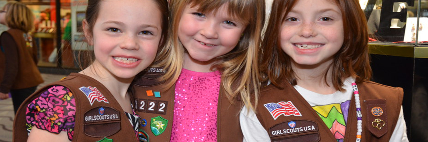 Three young girls smiling while wearing their Girl Scouts uniforms.