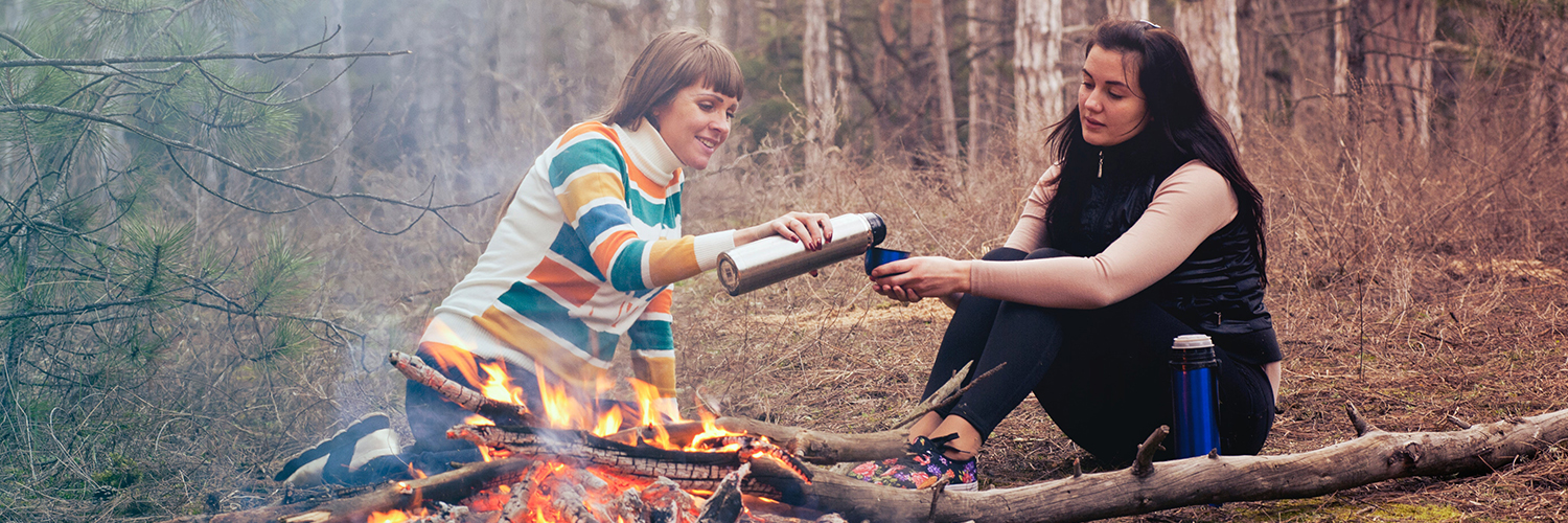 Two women sitting by the campfire having something to drink.
