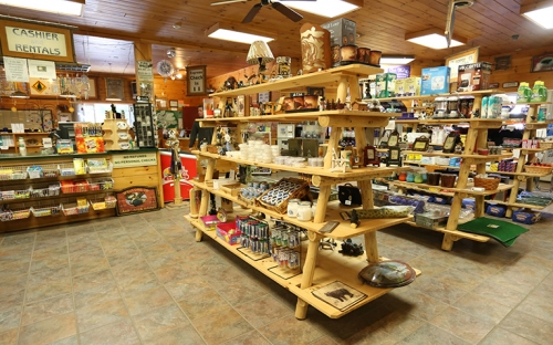The inside of a small Adirondack store with wooden shelves stocked with local goods