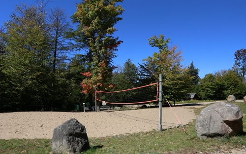 An outdoor volleyball court with trees to ones side a grass to the other with large boulders that you can sit on