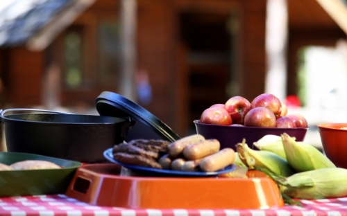 A picnic table with corn on the cob, hotdogs, hamburgers, and a bowl of apples on it with a wood cabin in the background
