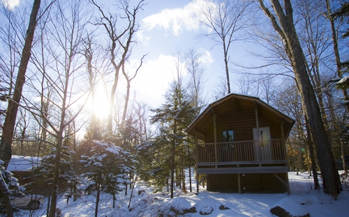 A cabin in the snow with the sun shining down