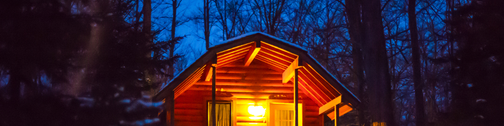 A wooden cabin at night time with the porch light on