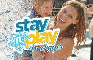 The stay 'n play logo. In the background of the picture are two guests smiling.