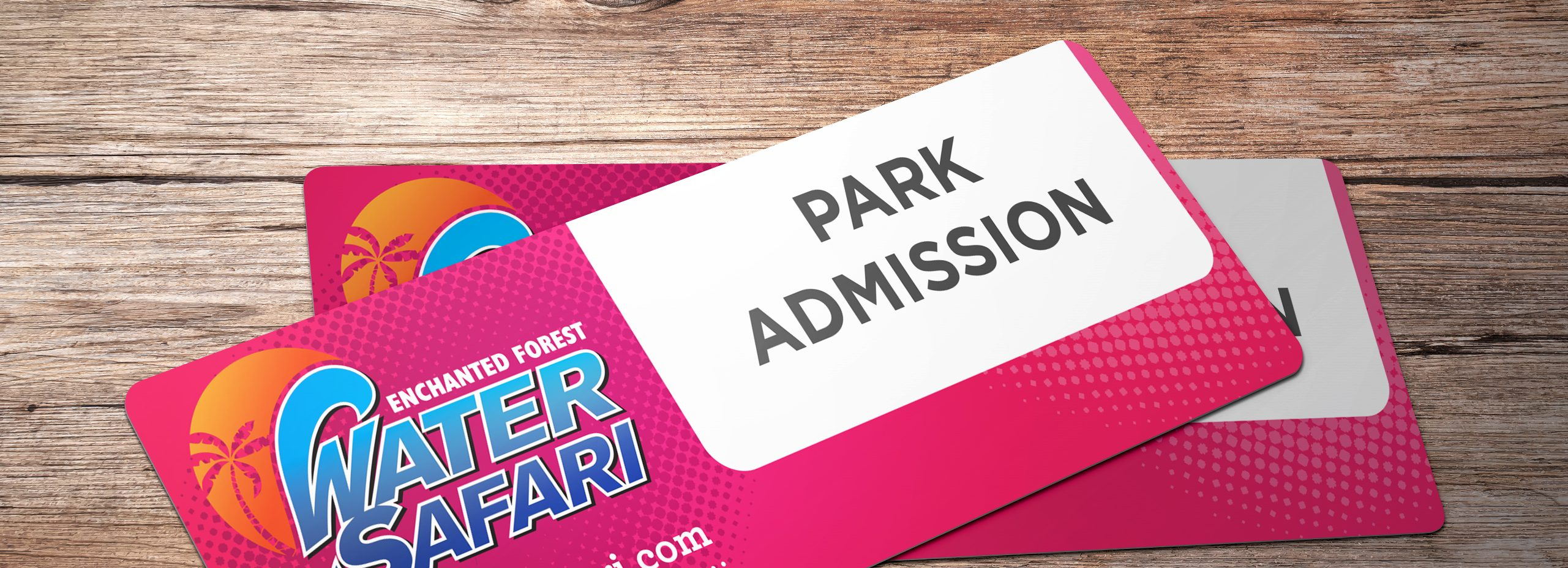 Two enchanted forest water safari park admission tickets against a wooden background