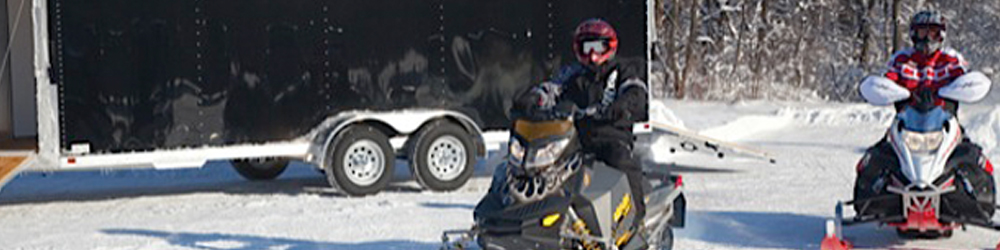 Two men on snowmobiles with a black trailer in the background