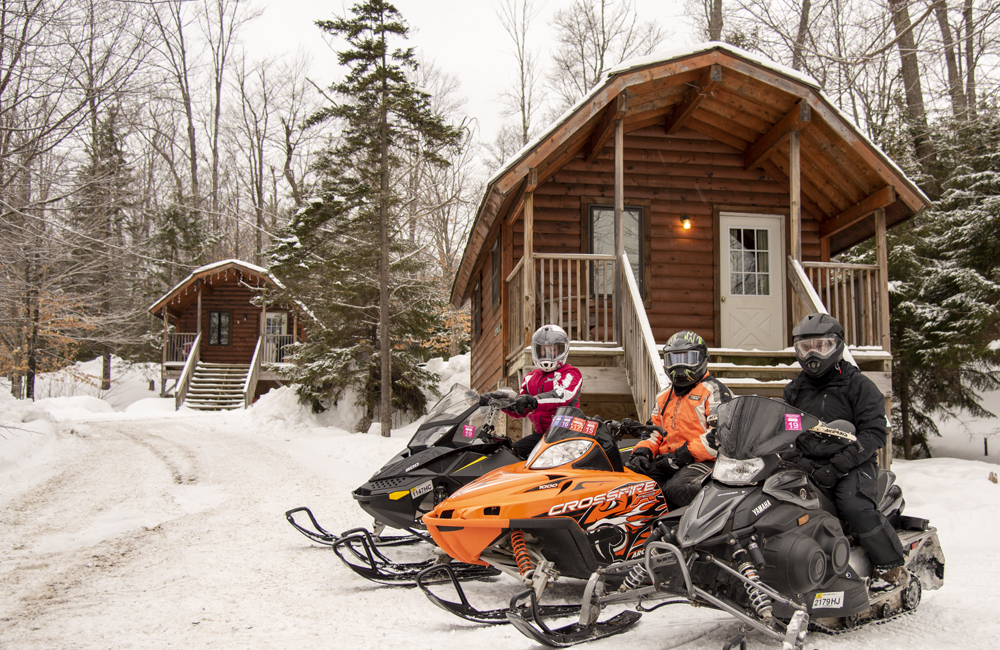 Three guests on their snowmobiles in front of their rental cabin.