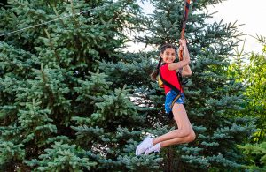 A girl smiling as she slides down the zip-line at Calypso's Cove.