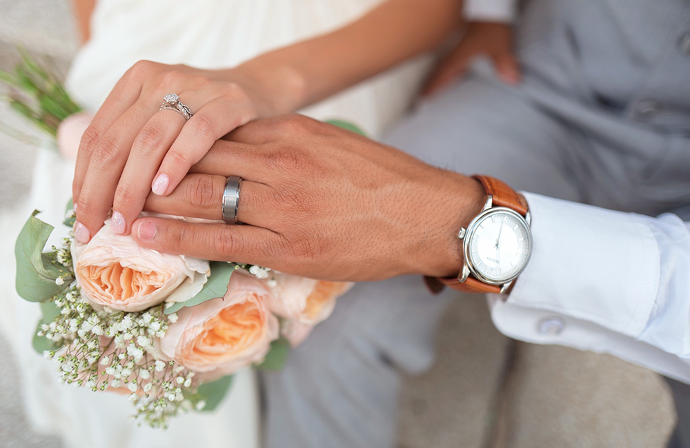 the hands of the bride and groom on the wedding bouquet