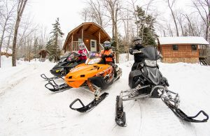 3 Snowmobilers in front of a Cabin