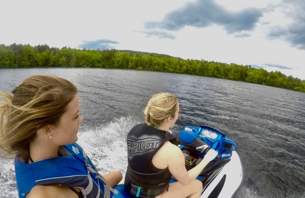 Two girls riding a jet-ski on the lake.