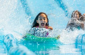 An excited young girl sliding down one of the water slides at Water Safari.